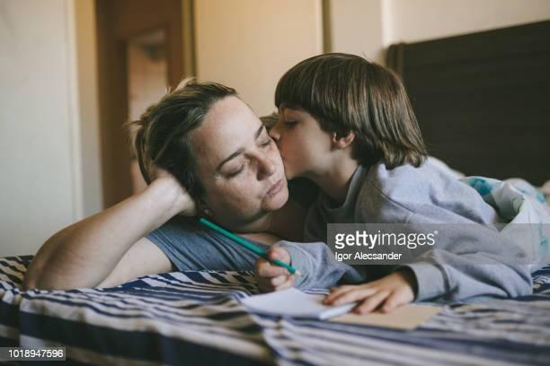 petit garçon baiser sa mère dans son lit - vie réelle photos et images de collection