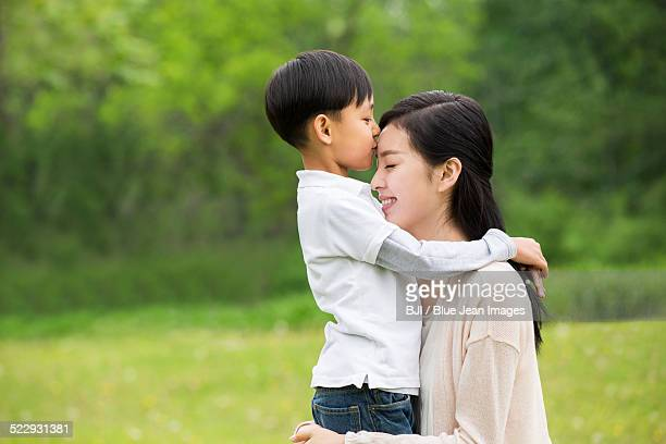 Little boy kissing his mother on forehead