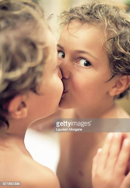 Little Boy Kissing His Reflection in Mirror