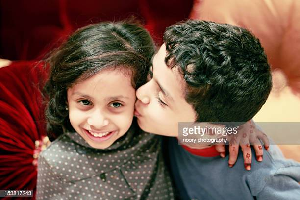 little boy kissing his sister - arabian girl kissing stock photos and pictures