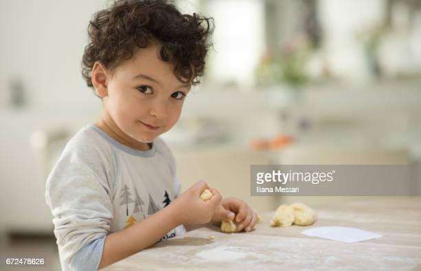 Little boy kneading bread dough