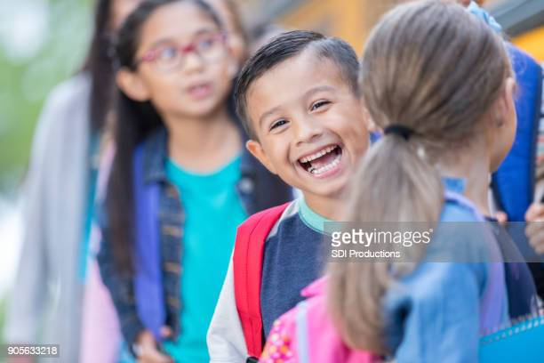 little boy laughs while waiting to board school bus - psa stock photos and pictures