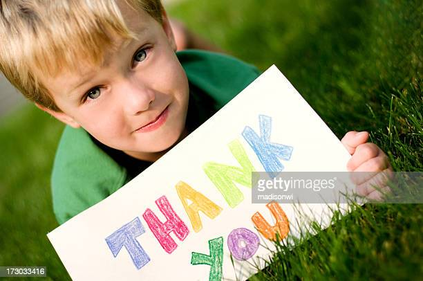 Little boy laying in grass holding a colored thank you sign