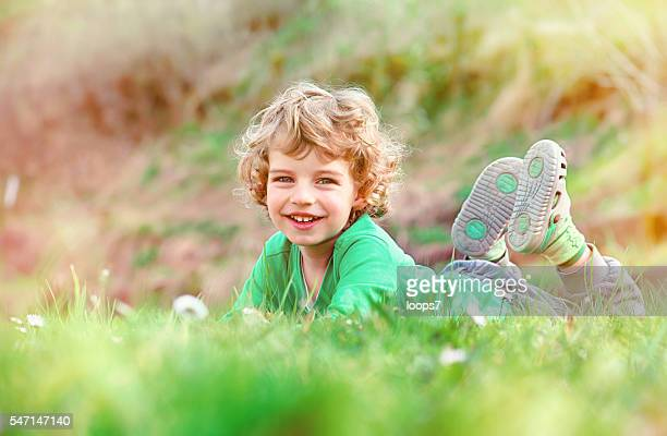 Little boy laying on a grass on meadow and smiling