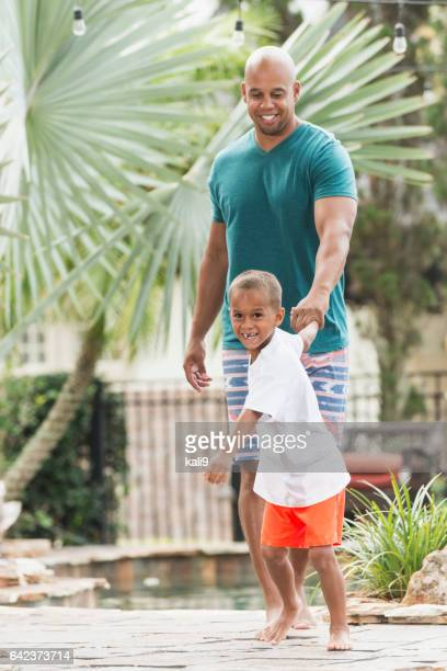 Little boy leading father, walking on resort pool deck