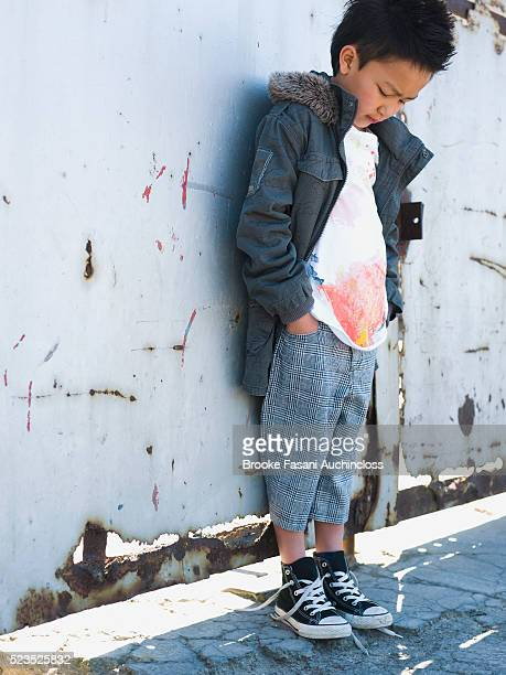 Little boy leaning against a wall