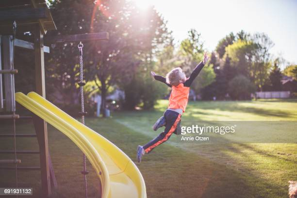Little boy Leaping from a Jungle Gym Slide