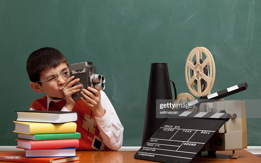 Little boy learning how to make film via video camera : Stock Photo