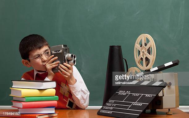 Little boy learning how to make film via video camera