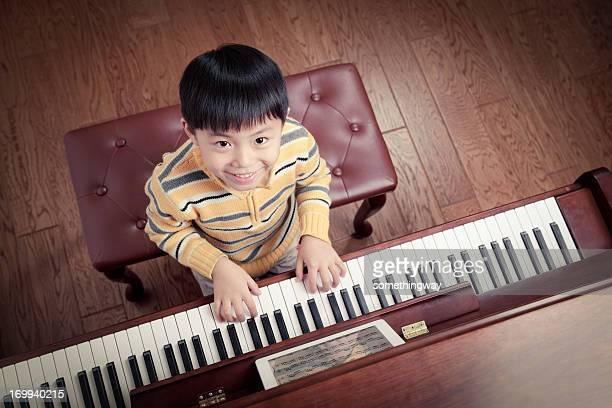 Little boy learning to play the piano