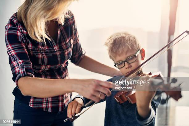 little boy learning to play violin. - violin stock pictures, royalty-free photos & images