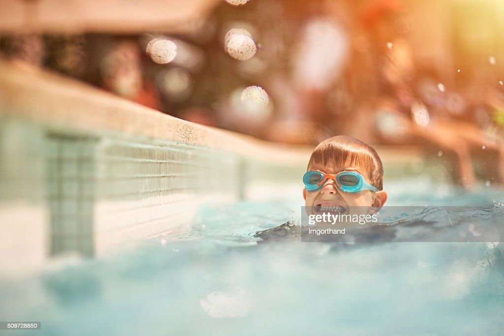 Little boy learning to swim in swimming pool : Stock Photo