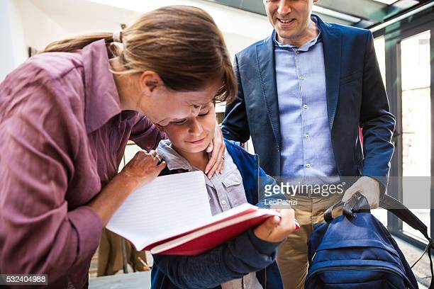Little boy leaving for school with parents in the morning