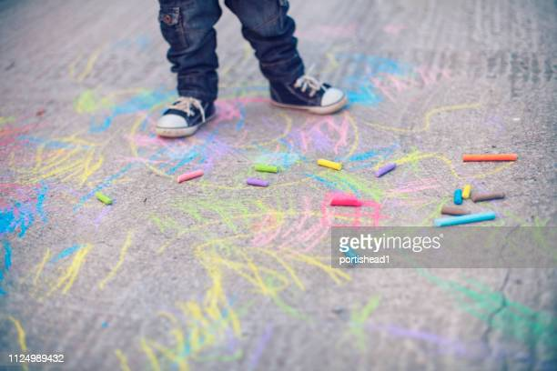 little boy legs and sidewalk chalks - chalk drawing stock pictures, royalty-free photos & images