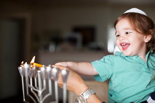 Little boy lighting a silver Menorah 187263866