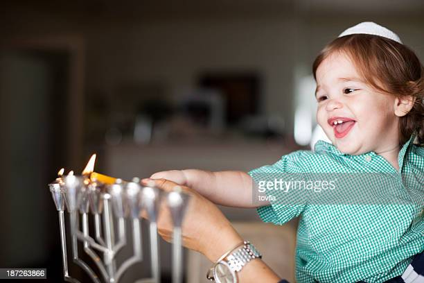 little boy lighting a silver menorah - judaism stock pictures, royalty-free photos & images