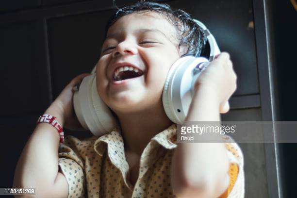 little boy listening music with headphone - innocence stock pictures, royalty-free photos & images