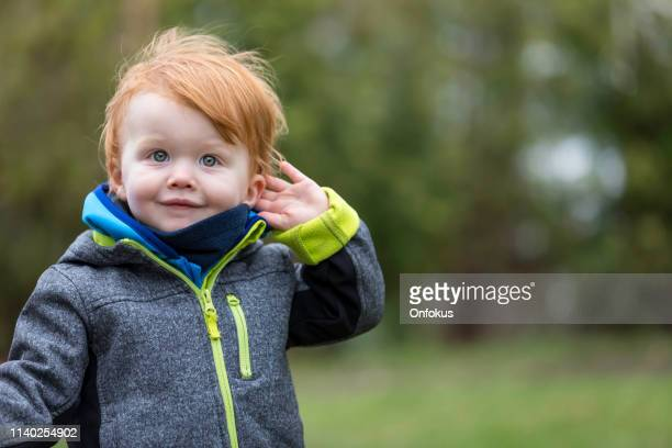 little boy listening to nature sounds outdoors - one baby boy only stock pictures, royalty-free photos & images