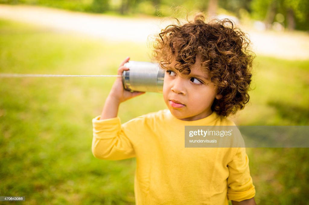 Little boy listening to sound through a tin can phone : Stock Photo