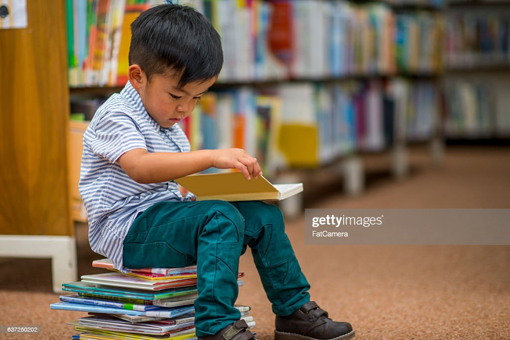 Little Boy Looking at Books : Stock Photo