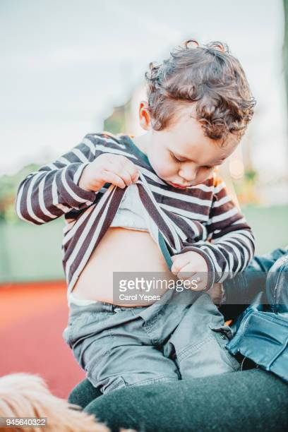 little boy looking at his belly button outdoors