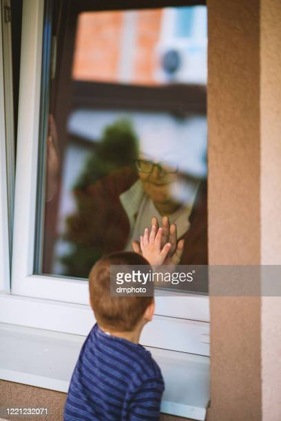 little boy looking at his grandmother at the window - shielding stock pictures, royalty-free photos & images