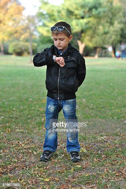 Little boy looking at his watch