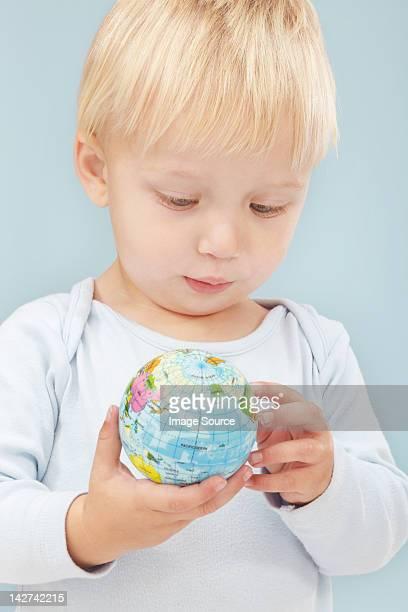 Little boy looking at little globe