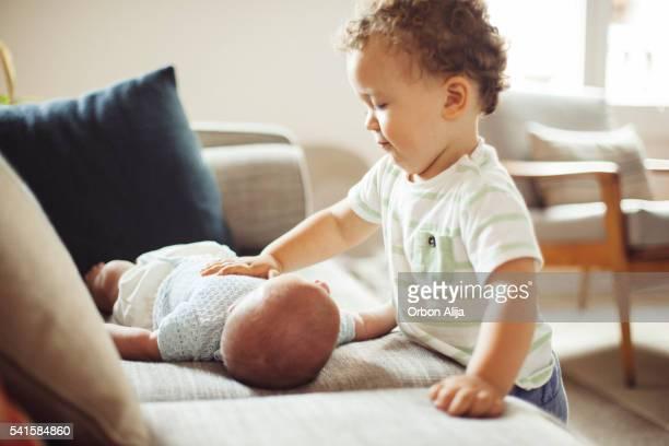 Niño pequeño observando a Bebé recién nacido