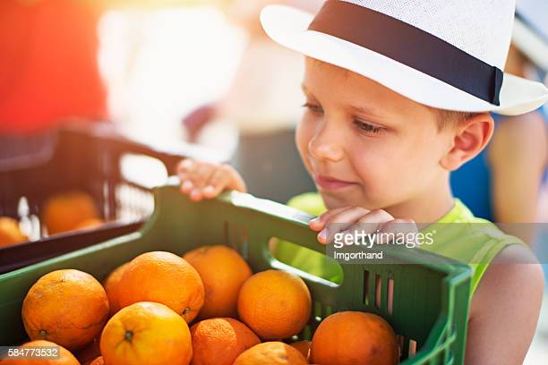 Little boy looking at oranges at the majorcan farmer's market