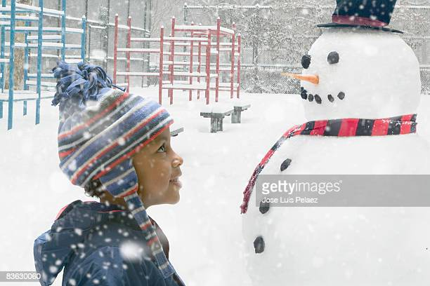little boy looking at snowman - snowman stock pictures, royalty-free photos & images