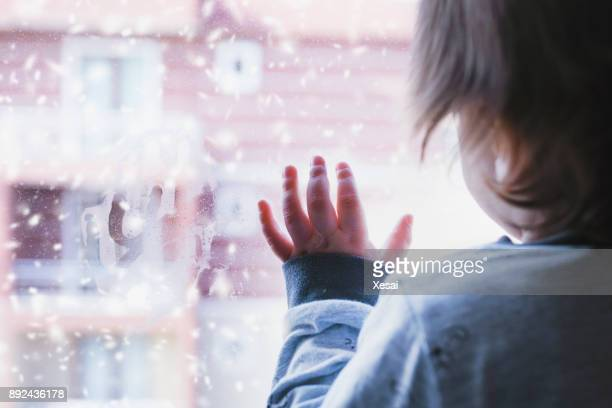 little boy looking out of the window on a snowy day - orphan stock pictures, royalty-free photos & images