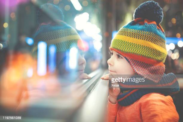 little boy looking out of the window - orphan stock pictures, royalty-free photos & images