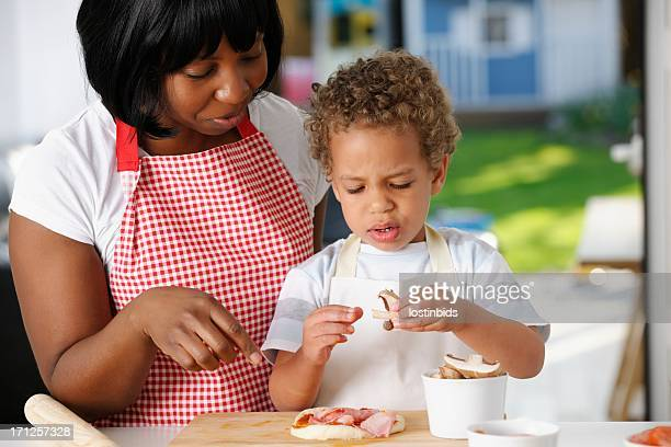 Little Boy Looking Puzzled While Preparing Pizza With His Mother
