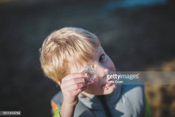 Little boy looking through a chunk of ice