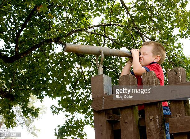 Little boy looking through a tube by a wooden gate