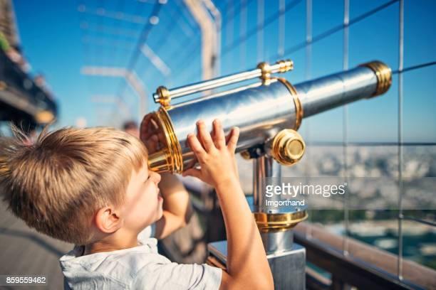 Petit garçon à la recherche par le biais de télescope de pièce de monnaie sur la Tour Eiffel