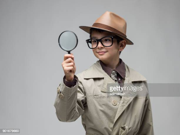 little boy looking through magnifying glass - detective stock pictures, royalty-free photos & images