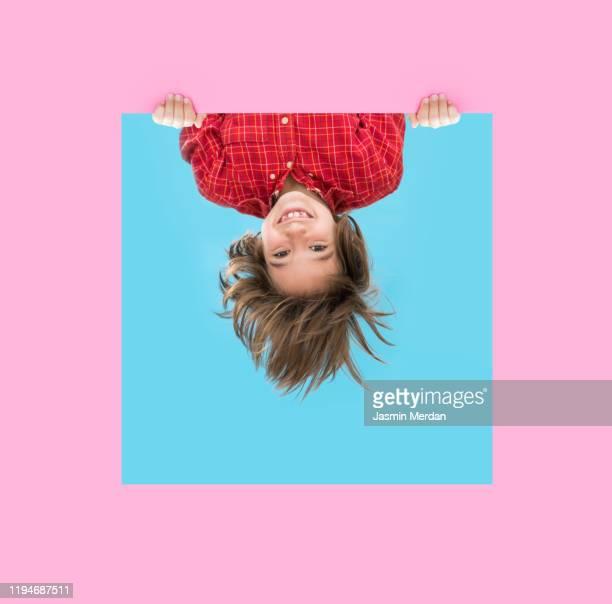 little boy looking through pink blue frame - auf den kopf gestellt stock-fotos und bilder