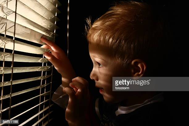 Little boy looking through window blinds