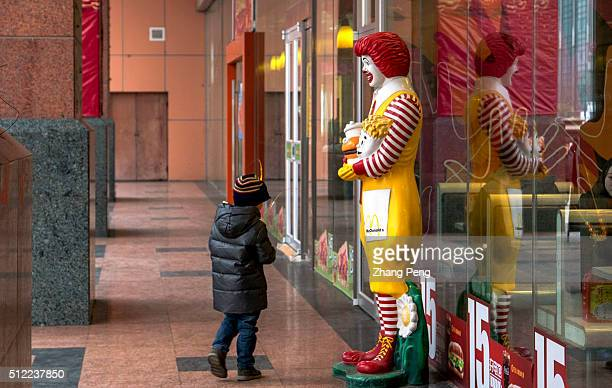 A little boy looks curiously at a figurine of Ronald McDonald stands outside a McDonald's restaurant McDonalds announced its fourthquarter samestore...