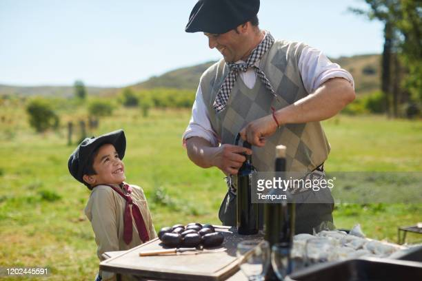 little boy looks happily at an older gaucho in a barbecue. - argentina stock pictures, royalty-free photos & images