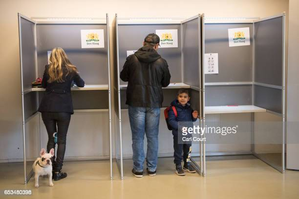 A little boy looks on as his father casts his vote next to a woman with a French bulldog in the Dutch general election on March 15 2017 in The Hague...