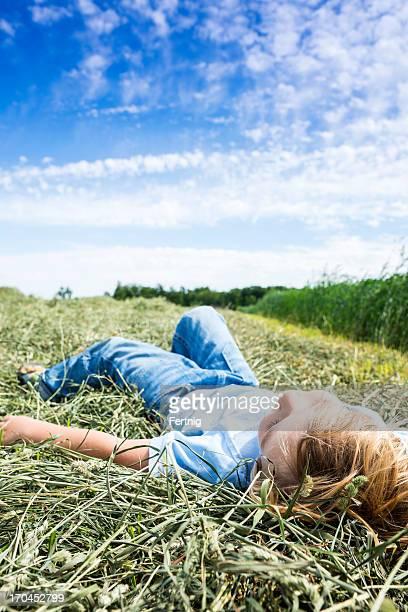 Kleine Junge liegt in einem frisch geschnittene hayfield