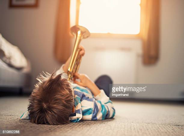 Little boy lying on back and playing trumpet