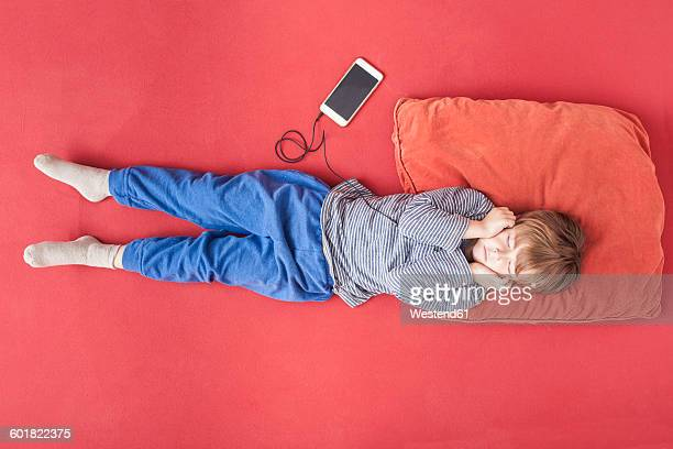 Little boy lying on bed hearing music with smartphone and earphones