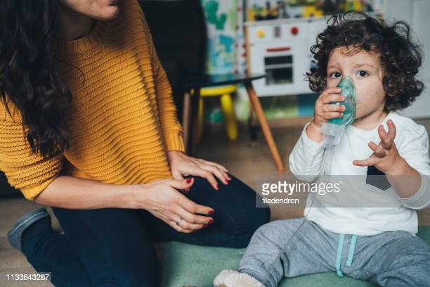 little boy makes inhalation at home - cystic fibrosis stock photos and pictures