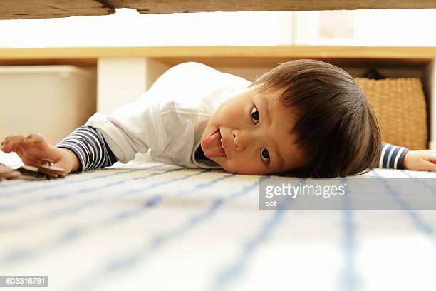 little boy making funny face under the table - under tongue stock pictures, royalty-free photos & images