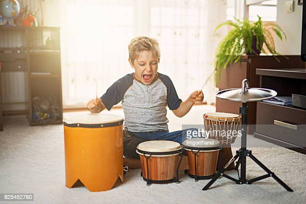 little boy making noise on makeshift drums - percussion instrument stock photos and pictures