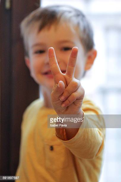 Little boy making peace sign